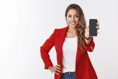 Studio shot pleasant smiling happy fair-haired caucasian girl smiling white teeth showing smartphone display screen royalty free stock photos