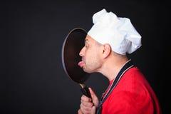 Studio shot of positive chef licks a frying pan. Royalty Free Stock Image