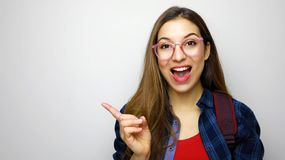 Studio shot of positive student girl on white background wearing glasses and backpack, pointing finger looking excited stock image