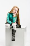Studio shot of pretty little girl. Sitting on a white cube Royalty Free Stock Photo