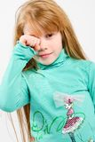 Studio shot of pretty little girl. Rubbing eyes with hand Royalty Free Stock Photography
