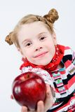 Studio shot of pretty little girl. Offering a red apple Stock Image