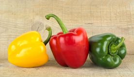 Studio shot of red,yellow,green bell peppers on woden plank Royalty Free Stock Photo