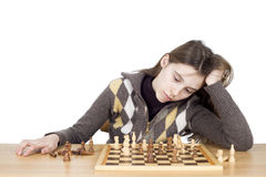 Studio Shot Of Sad Girl Leaning Her Head On Hand Trying To Concentrate On The Chess Game  On White. Background Stock Photos