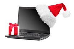 Studio shot of santa hat and gift on a laptop Stock Image