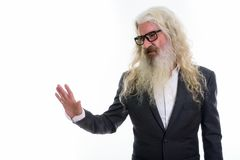 Studio shot of senior bearded businessman looking disgusted whil. E showing stop hand sign to the side royalty free stock images