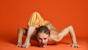 Studio shot of senior bearded man doing yoga poses and stretching his legs shirtless stock photo