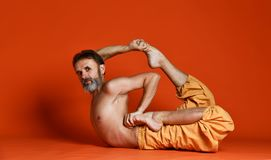 Studio shot of senior bearded man doing yoga poses and stretching his legs shirtless stock photography