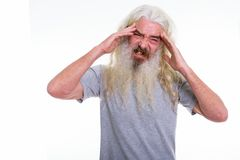 Studio shot of senior bearded man having headache with both hand. S on head royalty free stock photography