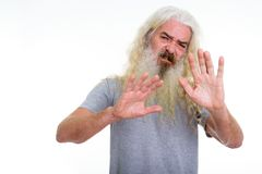 Studio shot of senior bearded man looking disgusted while showin. G stop hand sign with both hands stock photo