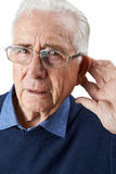 Studio Shot Of Senior Man Suffering From Deafness. Senior Man Suffering From Deafness Stock Images