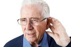 Studio Shot Of Senior Man Suffering From Deafness. Senior Man Suffering From Deafness Royalty Free Stock Photos