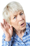 Studio Shot Of Senior Woman Suffering From Deafness. Senior Woman Suffering From Deafness Stock Photo