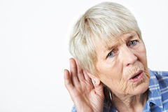 Studio Shot Of Senior Woman Suffering From Deafness. Senior Woman Suffering From Deafness Royalty Free Stock Photography