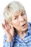 Studio Shot Of Senior Woman Suffering From Deafness. Senior Woman Suffering From Deafness Stock Photos