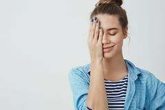 Studio shot sensual romantic good-looking dreamy 25s woman close eyes happily smiling covering half face palm, dreaming stock photos