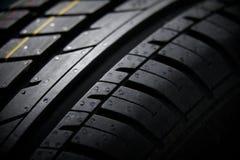 Studio shot of a set of summer car tires on black background. Contrasty lighting. Studio shot of a set of summer car tires on black background close up Royalty Free Stock Image