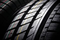 Studio shot of a set of summer car tires on black background. Contrasty lighting. Studio shot of a set of summer car tires on black background close up Royalty Free Stock Photos