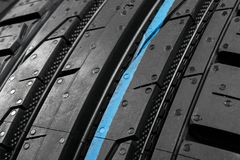 Studio shot of a set of summer car tires on black background. Tire stack background. Selective focus. Car tyre protector close up. Black rubber tire. Brand new royalty free stock images