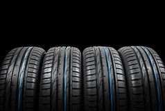 Studio shot of a set of summer car tires on black background. Tire stack background. Car tyre protector close up. Black rubber tir. E. Brand new car tires. Close royalty free stock image