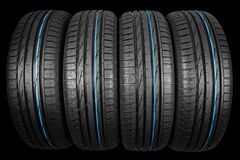 Studio shot of a set of summer car tires on black background. Tire stack background. Car tyre protector close up. Black rubber tir. E. Brand new car tires. Close royalty free stock images