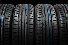 Studio shot of a set of summer car tires on black background. Tire stack background. Car tyre protector close up. Black rubber tir. E. Brand new car tires. Close stock photo