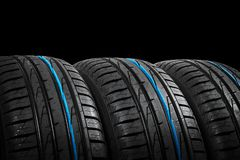 Studio shot of a set of summer car tires on black background. Tire stack background. Car tyre protector close up. Black rubber tir. E. Brand new car tires. Close stock photography