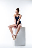 Studio shot of sexy ballet dancer sitting on cube Royalty Free Stock Images
