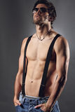 Studio shot of a sexy man with black suspenders and sunglasses Royalty Free Stock Image