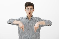 Studio shot of shocked amazed creative young guy with moustache in glasses, pointing down with index fingers, saying wow. And dropping jaw, seeing something stock photo