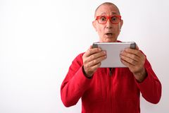 Studio shot of shocked bald senior man using digital tablet whil. E wearing eyeglasses against white background royalty free stock photos