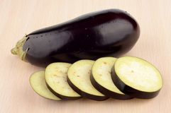 Studio shot single wet aubergine eggplant on wooden table Royalty Free Stock Photo