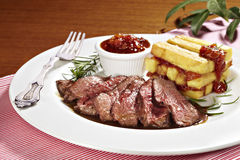 Sirloin steak with fried potatoes and tomato sauce. Studio shot of sirloin steak with fried potatoes and tomato sauce Stock Photos