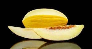 Studio shot of sliced Canary melon isolated black Stock Image