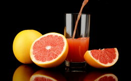 Studio shot sliced grapefruits with poured juice on black Royalty Free Stock Photos