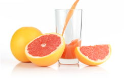 Studio shot sliced grapefruits with poured juice on white Royalty Free Stock Photos