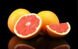 Studio shot sliced three grapefruits isolated black. Studio shot of sliced three grapefruits isolated black background Royalty Free Stock Photo