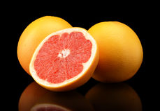 Studio shot sliced three grapefruits isolated black Royalty Free Stock Photos