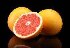 Studio shot sliced three grapefruits isolated black Royalty Free Stock Photos