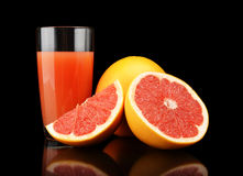 Studio shot sliced three grapefruits with juice isolated black Stock Photos
