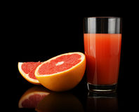 Studio shot sliced three grapefruits with juice isolated black Royalty Free Stock Image