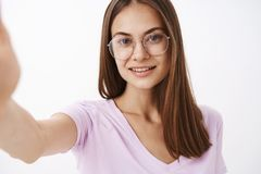 Studio shot of smart attractive and confident adult female entrepreneur in fancy glasses pulling hand forward and. Smiling at camera while taking selfie or stock images