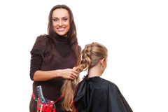 Studio shot of smiley hairdresser doing a plait Royalty Free Stock Photography