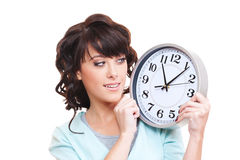 Studio shot of smiley woman looking at clock. Isolated on white Royalty Free Stock Photo