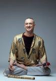Studio shot of smiling man doing yoga Stock Photography