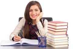 Studio shot of smiling schoolgirl doing her homework Royalty Free Stock Photography