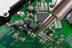 Studio shot of soldering iron and microcircuit Royalty Free Stock Photo