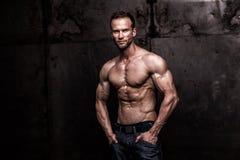 Strong athletic man on dark grunge background. Studio shot of strong athletic man on dark grunge background stock images