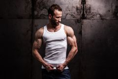 Strong athletic man on dark grunge background royalty free stock images