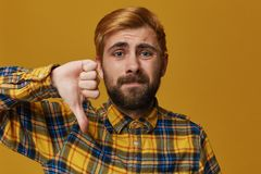Studio shot of stylish, bearded male with dyed blond gold hair shows sign of dislike. Negative expression and disapproval. Isolated over yellow studio Stock Photography
